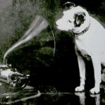 Original image of 'Dog looking at and listening to a phonograph'.